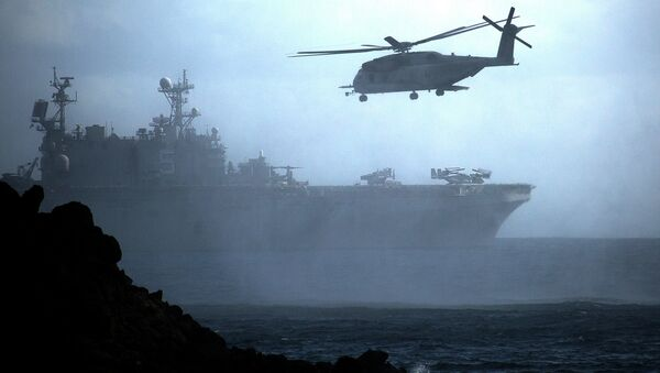 A CH-53E Super Stallion helicopter flies ahead of the amphibious assault ship USS Peleliu off the coast of Hawaii during Rim of the Pacific exercise in 2014. - Sputnik International