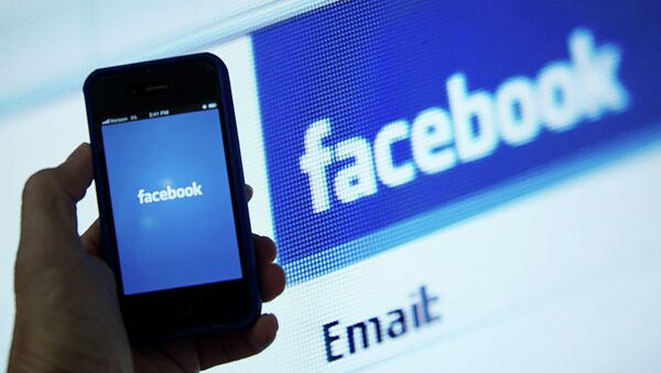 In this May 10, 2012 file photo, a view of and Apple iPhone displaying the Facebook app's splash screen in front of the login page on a computer are shown in Washington, DC - Sputnik International