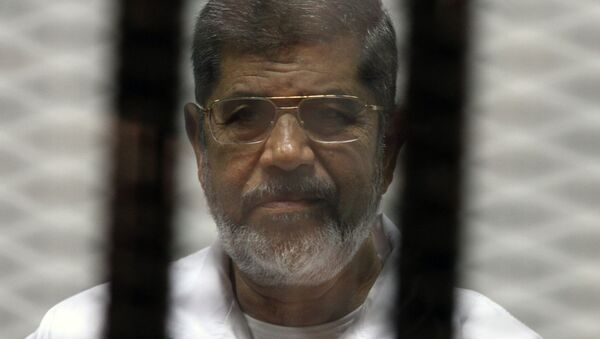 Egyptian ousted Islamist president Mohamed Morsi looks on from behind the defendants cage during is trial on May 8, 2014 - Sputnik International