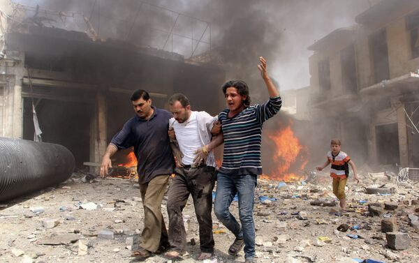 Syrian men help an injured person following a reported barrel bomb attack by Syrian government forces that hit an open market in the northern city of Aleppo, on June 3, 2015, killing and injuring people - Sputnik International