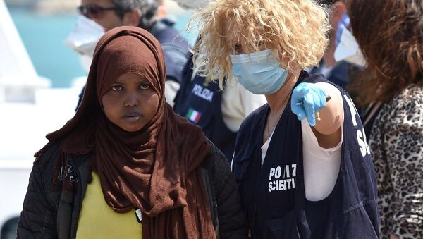 A forensic police officer gives indications to a woman as migrants arrived at Pozzallo's harbor near Ragusa, Sicily, Italy. - Sputnik International