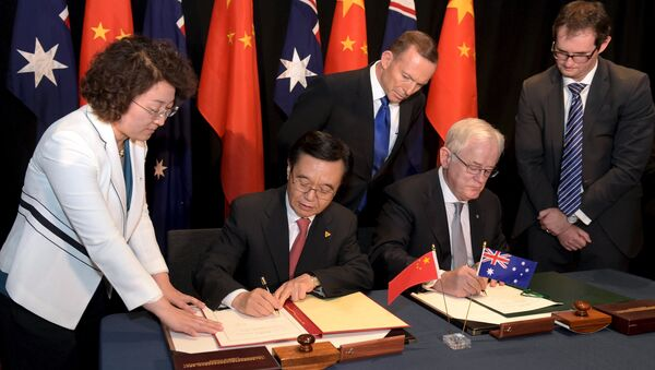 Australian Prime Minister Tony Abbott (C) watches as China's Minister of Commerce Gao Hucheng (2nd L) and Australian Minister for Trade Andrew Robb (2nd R) sign a trade agreement during an official signing ceremony in Canberra June 17, 2015 - Sputnik International