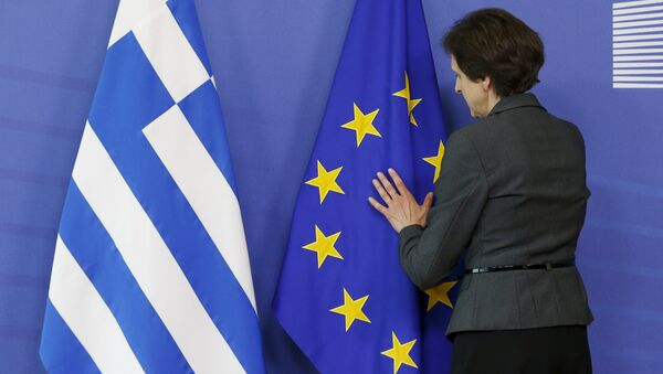 A worker adjusts flags ahead of the meeting between Greek Prime Minister Alexis Tsipras and European Commission President Jean-Claude Juncker at the EU Commission headquarters in Brussels, Belgium, June 3, 2015 - Sputnik International