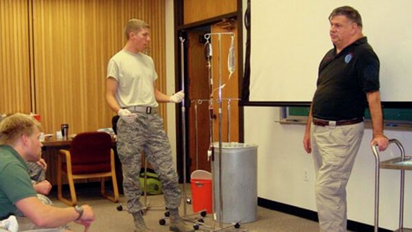 Dr. John Hagmann, right, teaches a course in treating battlefield trauma in this handout photograph taken around 2010 and released on June 17, 2015. - Sputnik International
