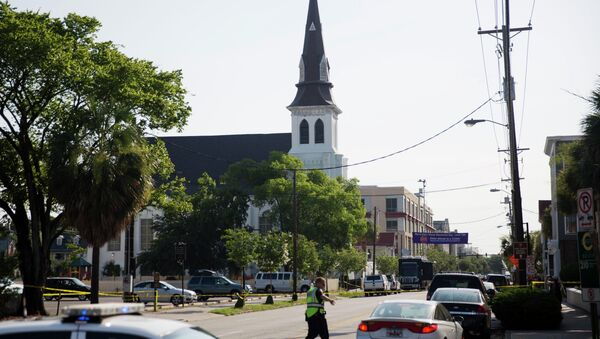 The steeple of Emanuel AME Church rises above the street as a police officer tells a car to move as the area is closed off following Wednesday's shooting, Thursday, June 18, 2015 in Charleston, S.C. - Sputnik International