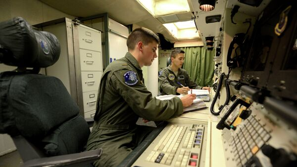 Oliver Parsons, left, and 1st Lt. Andy Parthum check systems in the underground control room where they work a 24-hour shift at an ICBM launch control facility near Minot. (File) - Sputnik International
