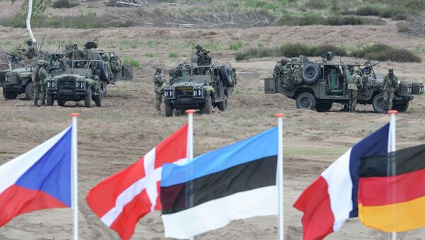 Flags wave in front of soldiers who take positions with their army vehicles during the NATO Noble Jump exercise on a training range near Swietoszow Zagan, Poland. file photo - Sputnik International