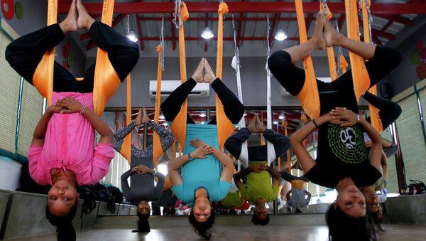 In this Thursday, June 18, 2015, photo, Indians perform anti gravity aerial yoga in Ahmadabad, India - Sputnik International