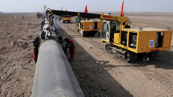 In this photo released by China's Xinhua News Agency, workers weld pipes at the construction site of the second project of west-to-east natural gas transmission pipeline in Fengle Town of Wuwei City, northwest China's Gansu Province, on Monday, March 10, 2008 - Sputnik International