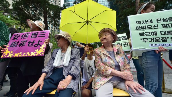 South Korean former comfort women Kim Bok-Dong (L) and Gil Won-Ok (R), who were forced to serve as sex slaves for Japanese troops during World War II, sit under a yellow umbrella during a press conference outside the Japanese embassy in Seoul on June 23, 2015 - Sputnik International