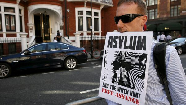 A supporter of Wikileaks founder Julian Assange holds a placard with his mouth during a gathering outside the Ecuador embassy in London, Britain June 19, 2015 - Sputnik International