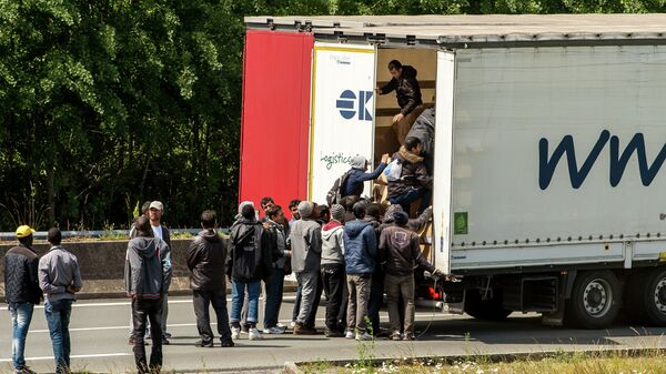 Migrants climb in the back of a lorry on the A16 highway leading to the Eurotunnel on June 23, 2015 in Calais, northern France - Sputnik International