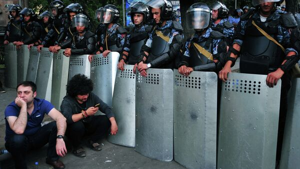 Demonstrators sit on a street in front of a line of riot police during a protest against an increase of electricity prices in the Armenian capital Yerevan on June 24, 2015 - Sputnik International