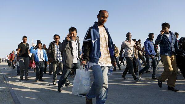 Migrants walk after disembarking from the Spanish Civil Guard's ship Rio Segura, in the Sicilian harbour of Augusta, Italy, June 23, 2015 - Sputnik International