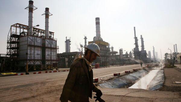 An Iranian oil worker makes his way through Tehran's oil refinery south of the capital Tehran, Iran, Monday, Dec. 22, 2014 - Sputnik International
