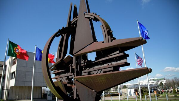 The NATO symbol and flags of the NATO nations outside NATO headquarters in Brussels on Sunday, March 2, 2014 - Sputnik International