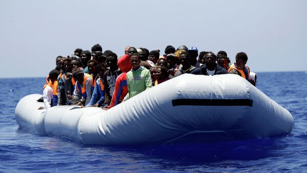A rubber boat loaded of migrants is seen during a search and rescue mission in the Mediterranean Sea off the Libyan coasts, Italy, Tuesday, June 23, 2015 - Sputnik International