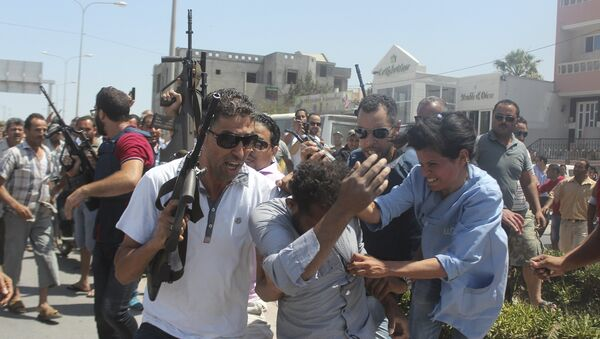 Police officers control the crowd (rear) while surrounding a man (front C) suspected to be involved in opening fire on a beachside hotel in Sousse, Tunisia, as a woman reacts(R), June 26, 2015 - Sputnik International