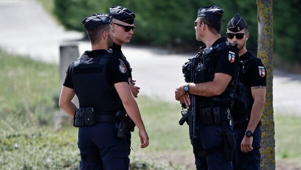 Police officers guard the road leading to a plant where an attack took place in Saint-Quentin-Fallavier, southeast of Lyon, France, Friday, June 26, 2015 - Sputnik International