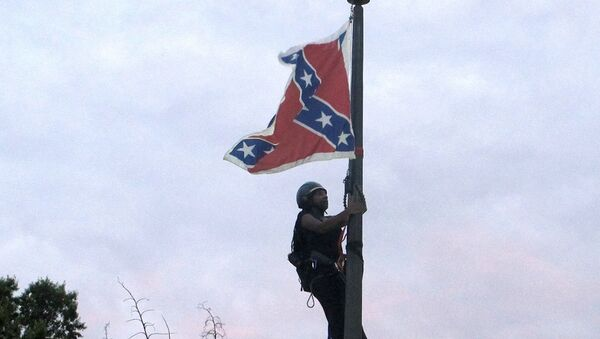 Bree Newsome of Charlotte, N.C., climbs a flagpole to remove the Confederate battle flag at a Confederate monument in front of the Statehouse in Columbia, S.C., on Saturday, June, 27, 2015. - Sputnik International
