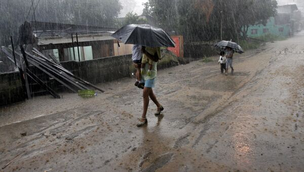 A woman carries her children in the rain as she walks by homes destroyed by flooding in Alajuela, Costa Rica - Sputnik International