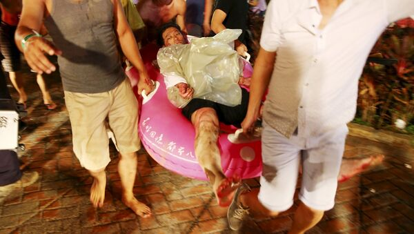 People carry an injured victim from an accidental explosion during a music concert at the Formosa Water Park in New Taipei City, Taiwan, June 27, 2015 - Sputnik International