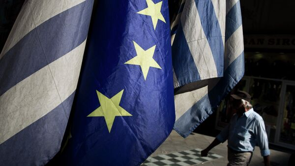A man walks past a European and Greek flags in central Athens, on Tuesday, June 30, 2015. - Sputnik International