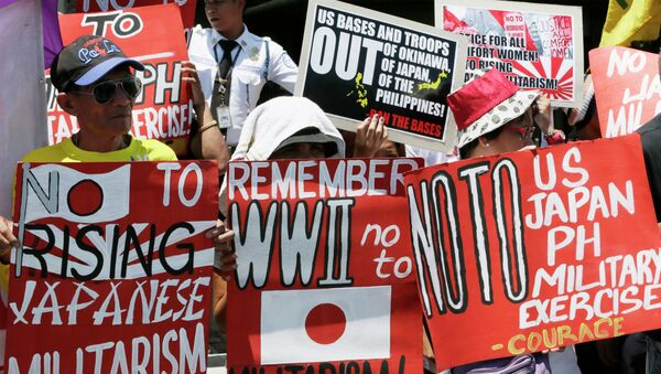 Protesters display placards during a rally outside the Japanese Embassy to protest the ongoing naval exercises by Japan and the United States. - Sputnik International