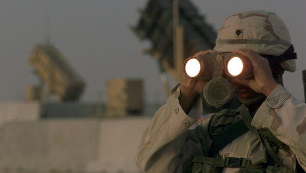 US soldier uses a pair of binoculars to scans the landscape around his Patriot Missiles based at Al Udeid AB, Qatar - Sputnik International