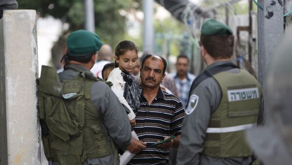 A Palestinian man carrying his daughter shows his identity card to Israeli border policemen at an Israeli checkpoint in the West bank city of Bethlehem June 26, 2015 - Sputnik International