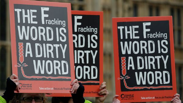 Demonstrators hold up placards as they take part in an anti-fracking protest outside the Palace of Westminster in London. - Sputnik International