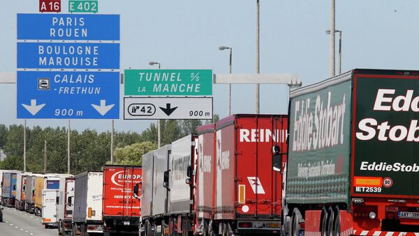 Trucks are stuck in a traffic jam on a highway leading to the Channel tunnel after striking workers invaded the Eurotunnel train tracks in Calais, northern France, in a protest against job cuts, Tuesday, June 30, 2015. - Sputnik International