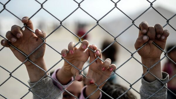 Hands of Syrian Kurdish children are seen holding a fence in a UNHCR (United Nations Refugee Agency) refugee camp on February 2, 2015, at Suruc, in Sanliurfa - Sputnik International