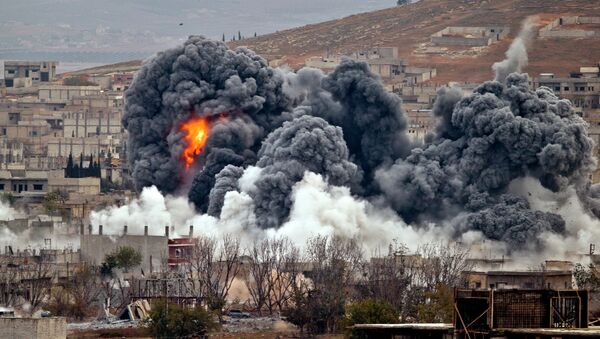 Smoke rises from the Syrian city of Kobani, following an airstrike by the US led coalition, seen from a hilltop outside Suruc, on the Turkey-Syria border Monday, Nov. 17, 2014. - Sputnik International