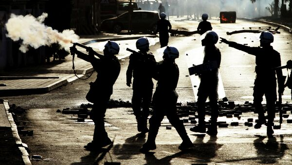 Riot police fire tear gas toward anti-government protesters, unseen, in Jidhafs, Bahrain, on Friday, March 15, 2013 - Sputnik International