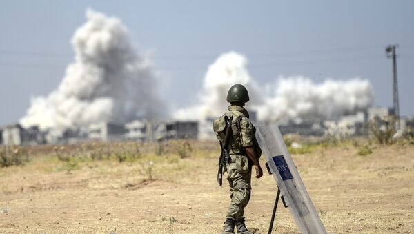 A picture taken from the Turkish side of the border in Suruc, Sanliurfa province, shows a Turkish solider standing as smoke rises from the Syrian town of Kobane, also known as Ain al-Arab, on June 27, 2015 - Sputnik International