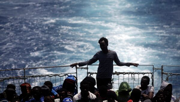 Migrants sit on the deck of the Belgian Navy vessel Godetia after they were saved at sea during a search and rescue mission in the Mediterranean Sea off the Libyan coasts, Wednesday, June 24, 2015. - Sputnik International