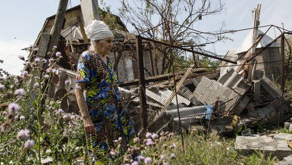 A woman walks past her damaged house, which according to locals was hit by shelling on Wednesday, the village of Sakhanka in Donetsk region, Ukraine, July 2, 2015 - Sputnik International