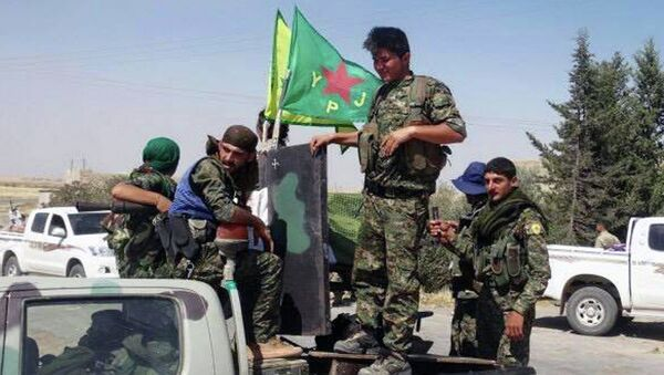 In this photo provided by the Kurdish fighters of the People's Protection Units (YPG), which has been authenticated based on its contents and other AP reporting, Kurdish fighters of the YPG, sit on their pickup in the town of Ein Eissa, north of Raqqa city, Syria, Tuesday, June 23, 2015 - Sputnik International