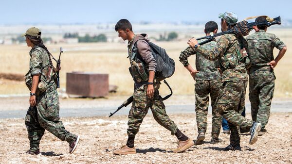 Kurdish People's Protection Units (YPG) fighters walk with their weapons at the eastern entrances to the town of Tal Abyad in the northern Raqqa countryside, Syria, June 14, 2015 - Sputnik International