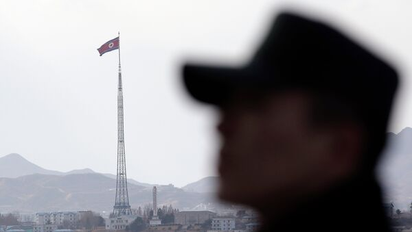 A South Korean soldier stands as a North Korean flag flutters in the wind atop a 160-meter (533-foot) tower in the village of Gijungdong near the north side of the border village of Panmunjom, which has separated the two Koreas since the Korean War, in Paju, north of Seoul, South Korea, Wednesday, Nov. 12, 2014 - Sputnik International