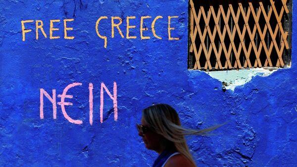 A tourist passes a graffiti in the Plaka tourist district of Athens, Greece - Sputnik International