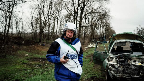 An International observer of the Organization for Security and Co-operation in Europe (OSCE) stands next to a destroyed car after shelling during an inspection tour near the village of Shirokino - Sputnik International