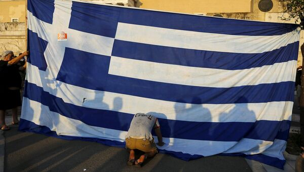 A protester kneels to pay his respect in front of a Greek flag during an anti-austerity rally in Athens, Greece, June 29, 2015 - Sputnik International