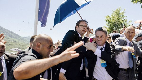 Bodyguards try to protect Serbian Prime Minister Aleksandar Vucic (C) from stones hurled at him by an angry crowd at the Potocari Memorial Center, near the eastern Bosnian town of Srebrenica on July 11, 2015 - Sputnik International