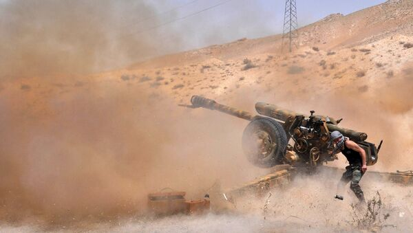 A Syrian army soldier fires artillery shells towards Islamic State (IS) group jihadists in northeastern Palmyra on May 17, 2015 - Sputnik International