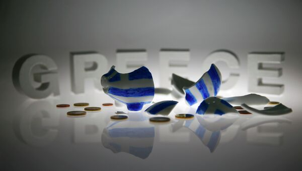 A broken piggybank painted in the colours of the Greek flag lies amongst various euro coins in front of letters spelling the word 'GREECE' in this picture illustration taken in Berlin, Germany June 30, 2015 - Sputnik International