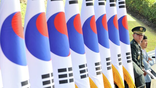 A South Korean military officer (R) stands next to a line of national flags during a ceremony to mark the 64th Korea Armed Forces Day at the military headquarters in Gyeryong, about 140 km south of Seoul, on September 25, 2012 - Sputnik International