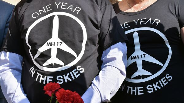 People wearing t-shirts bearing a drawing of a plane and slogans reading  MH 17, One year in the skies hold flowers to the Dutch embassy in Kiev on July 17, 2015 - Sputnik International