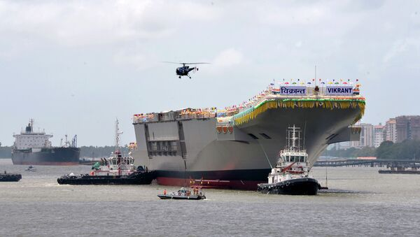 Tugs guide the home-built aircraft carrier INS Vikrant as it leaves the Cochin Shipyard's dock after its launch in Kochi on 12 August 2013. - Sputnik International